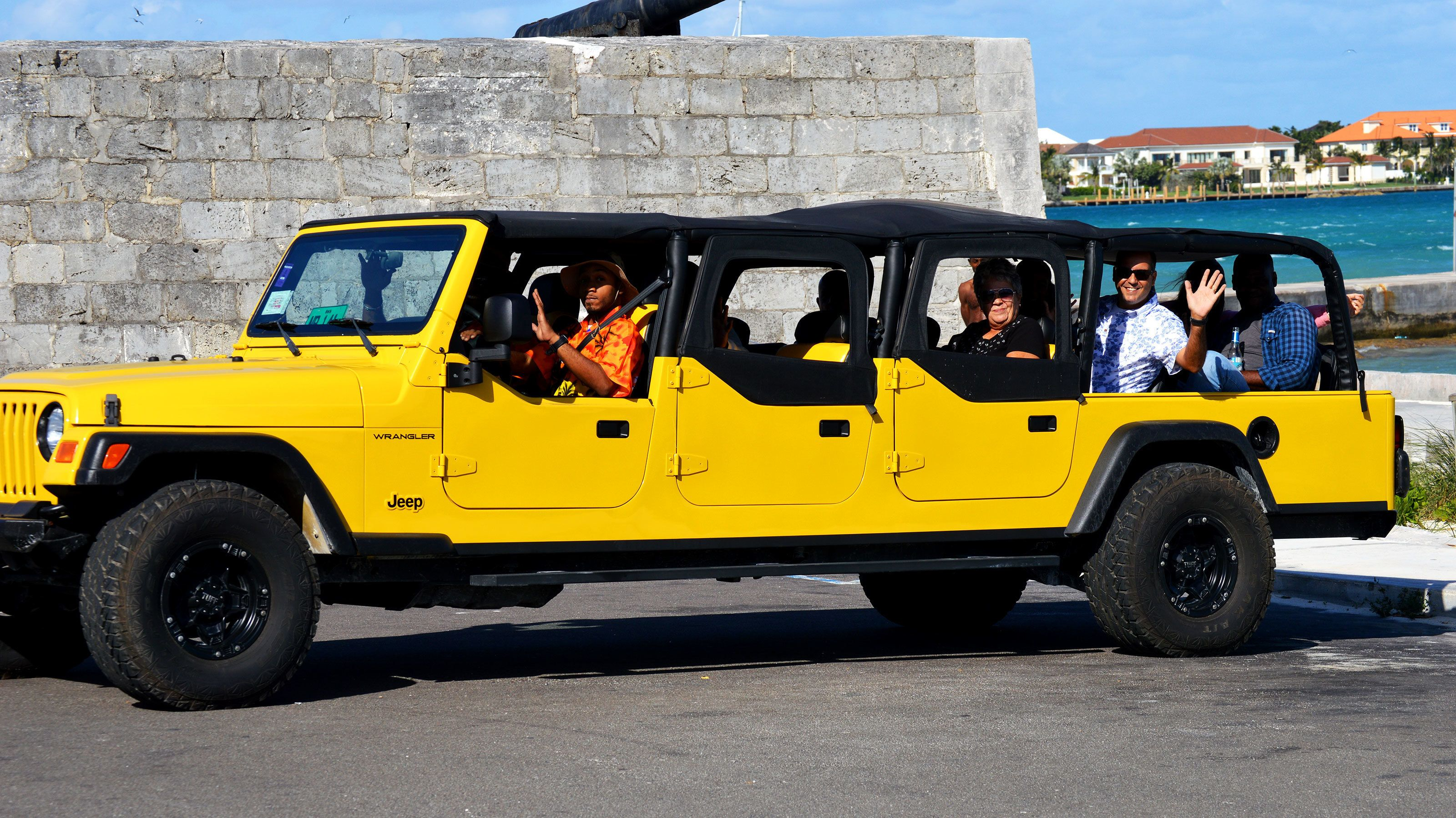 Tour group sit in jeep near beach in Nassau