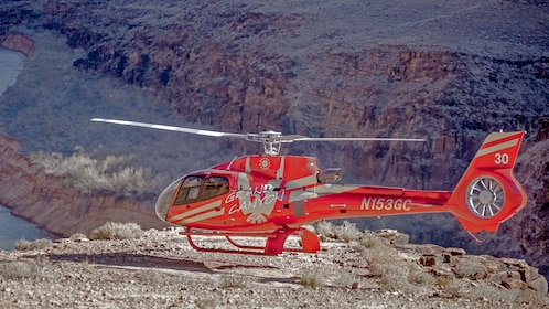 Helicopter about to land on edge of Grand Canyon