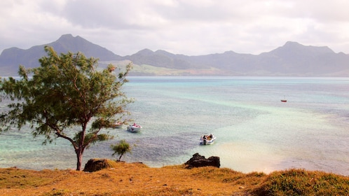 View from peninsula of tour speedboats float on clear waters in Mauritius