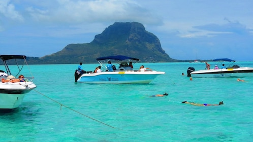 Snorklers swim around three tour boats in Mauritius