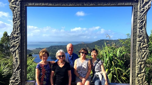 Group of people posing for picture around giant picture frame on hill peak in New Zealand