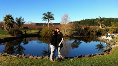 Two girls having picture taken in front of pond and vineyard in New Zealand