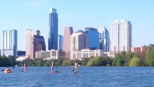 Kayakers and paddle boarders on river with Austin skyline in background