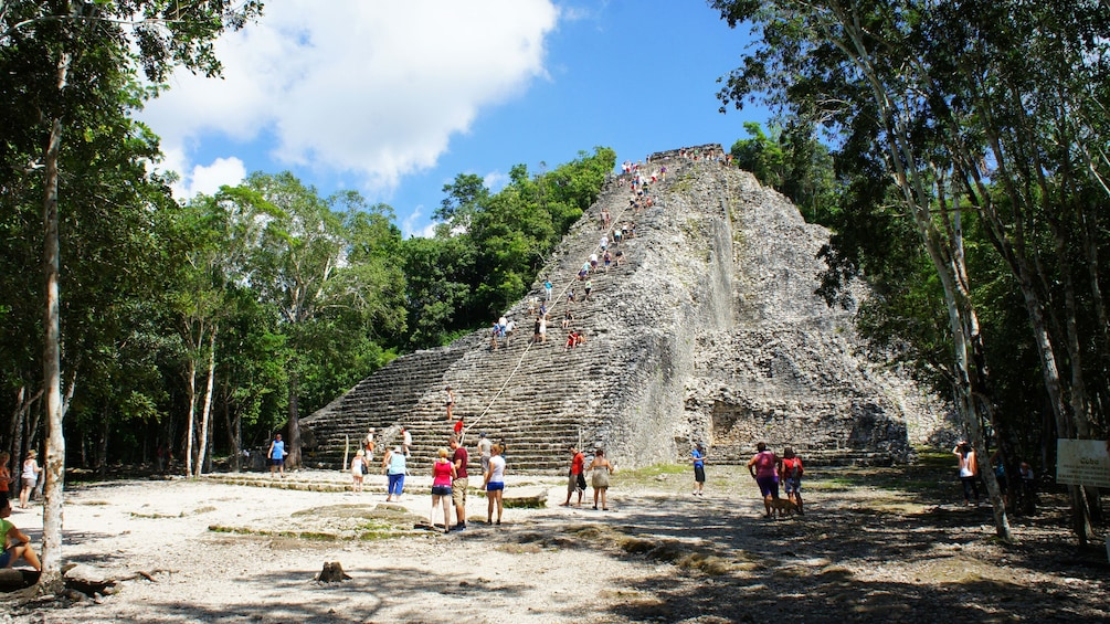 Show item 1 of 9. Tourists at temple ruins in Tulum