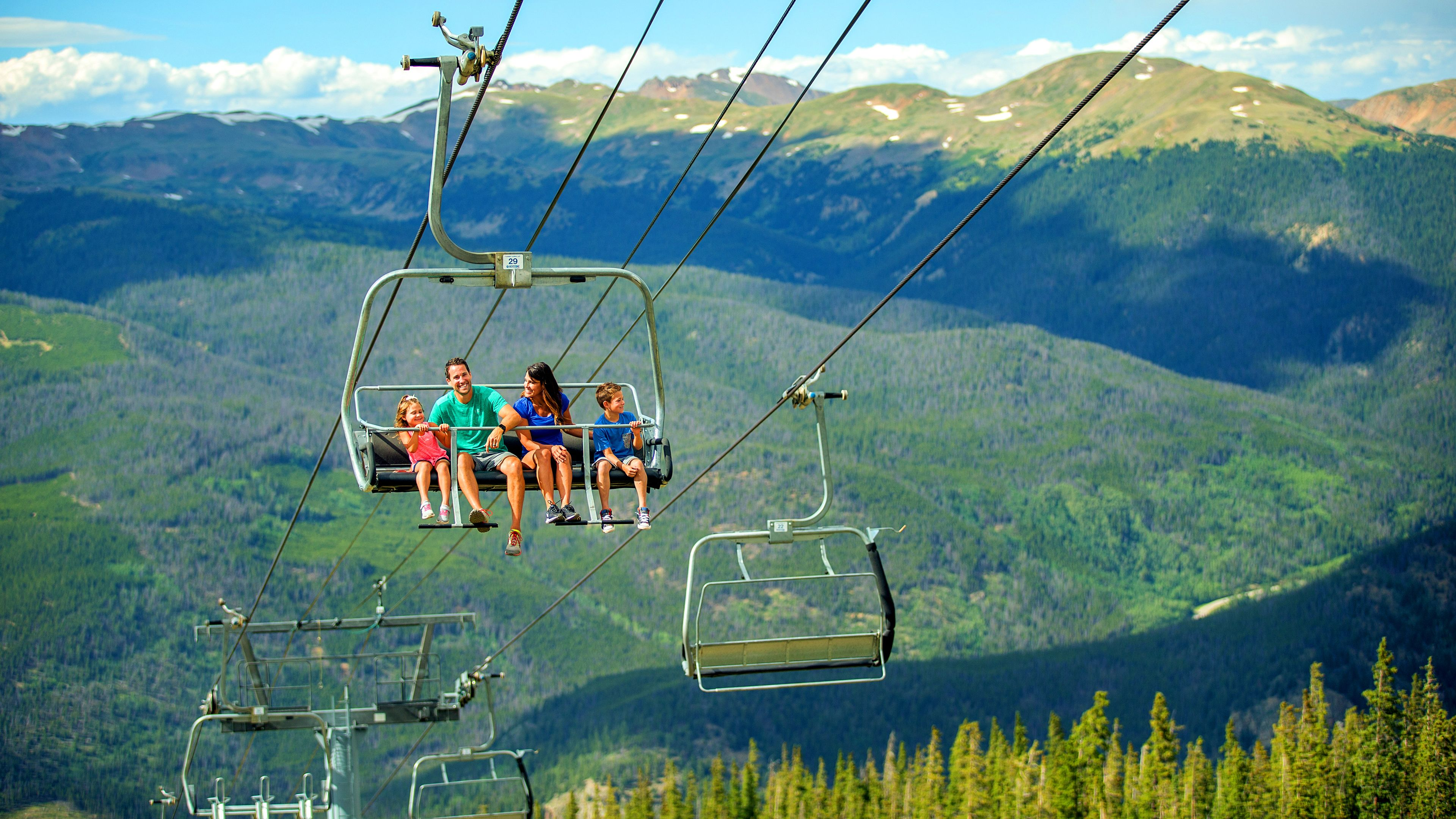 Family rides a gondola on a sunny mountaintop