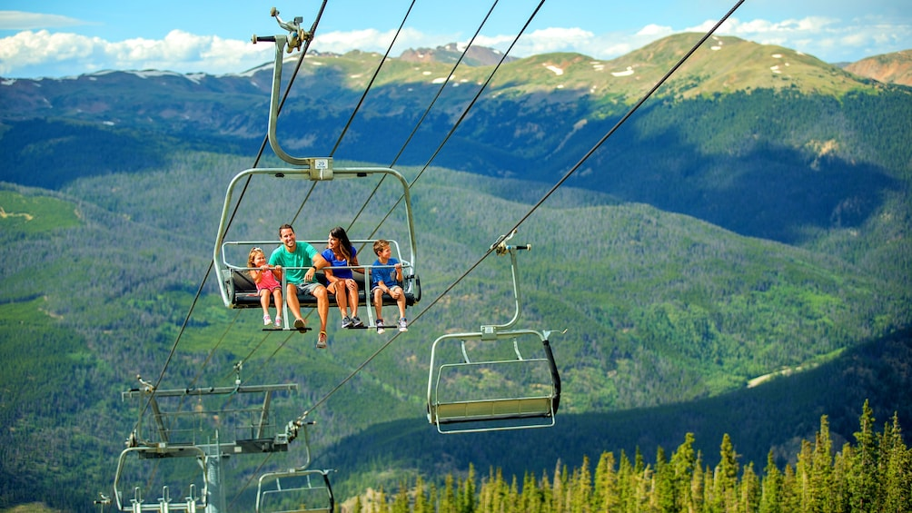 Show item 2 of 5. Family rides a gondola on a sunny mountaintop