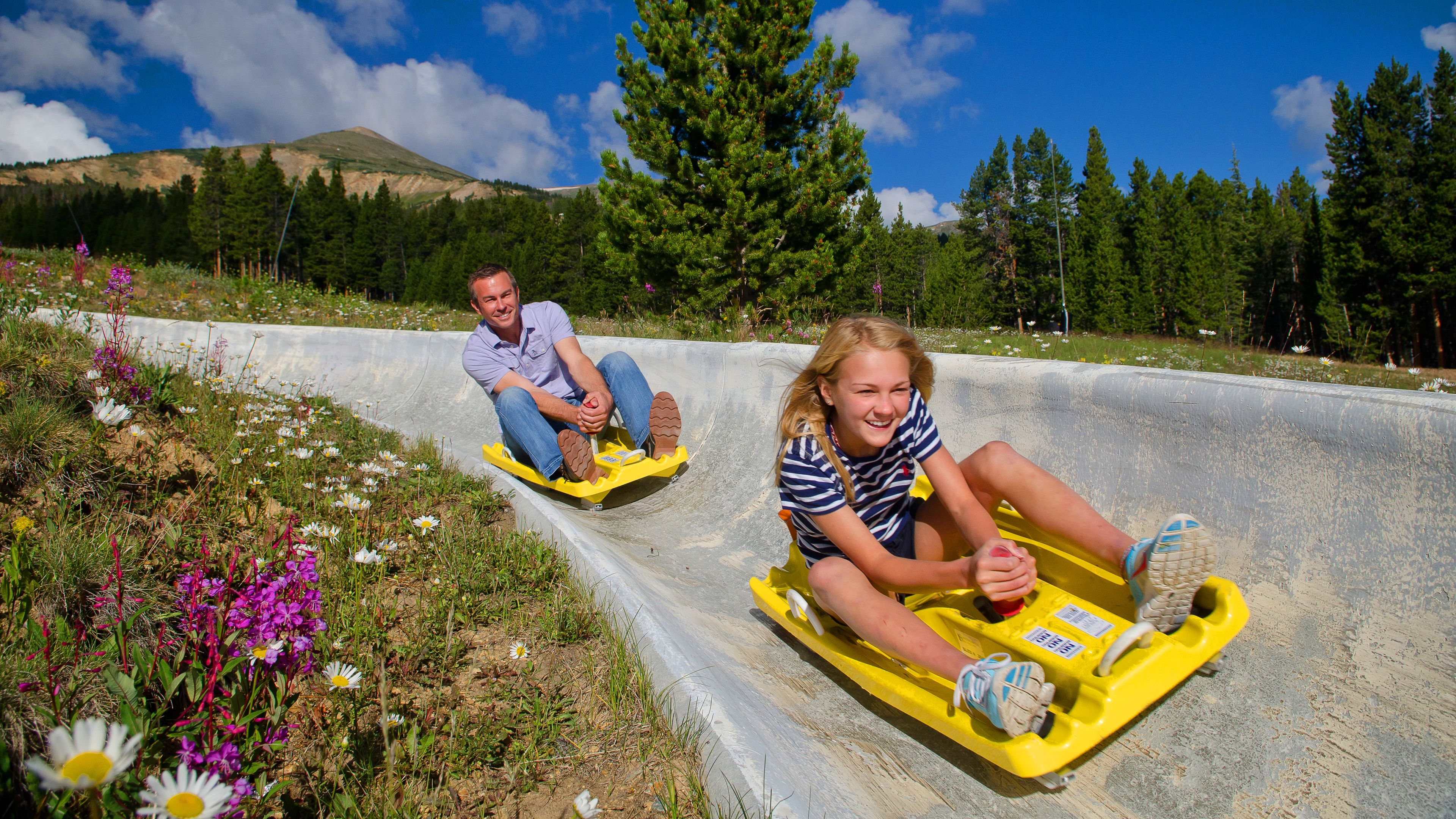 Man and girl ride carts down a concrete track