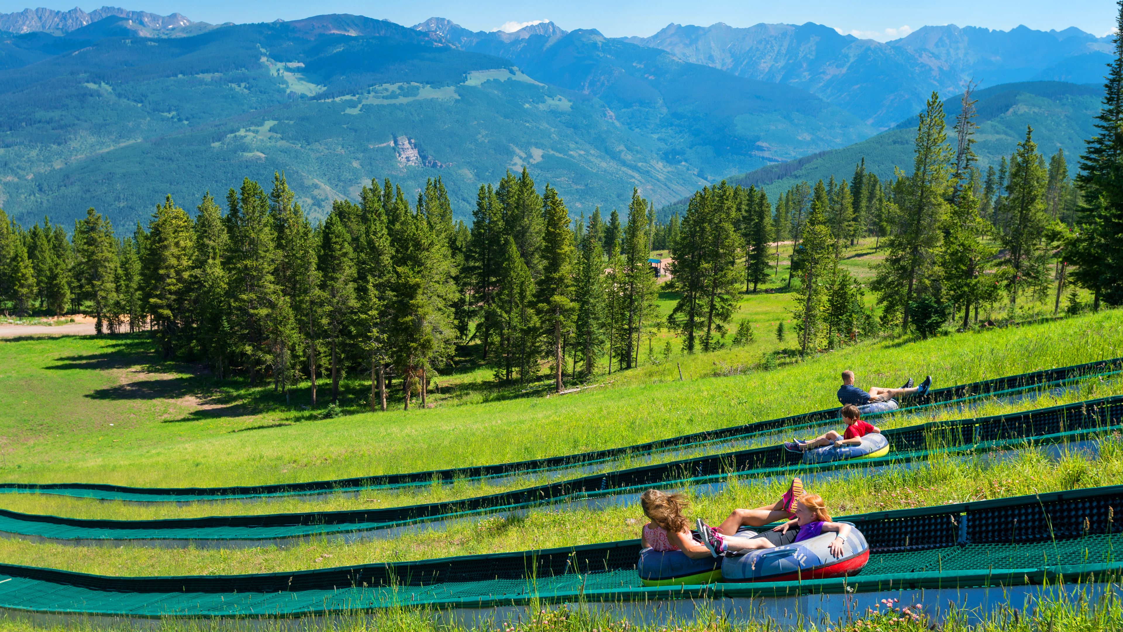 Groups of people tubing down a mountain in the Rockies in the summer