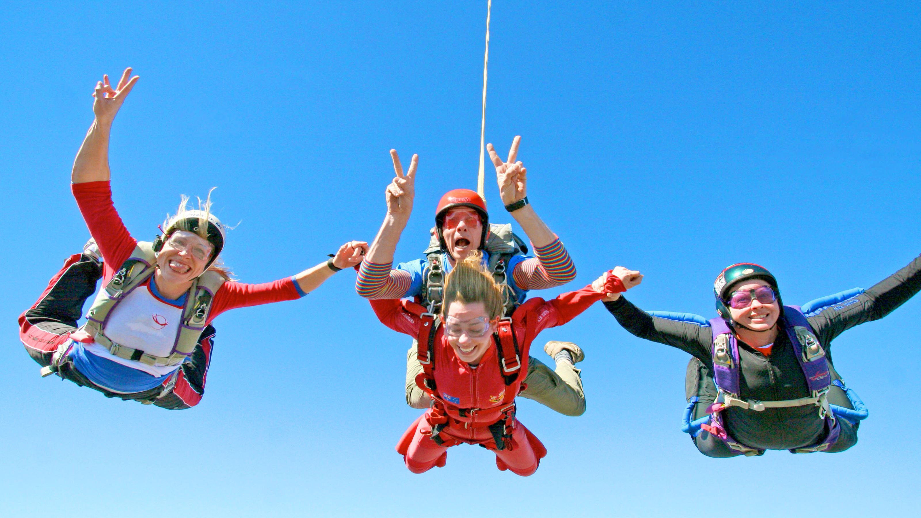Skydivers in a group free falling over Sunshine Coast.