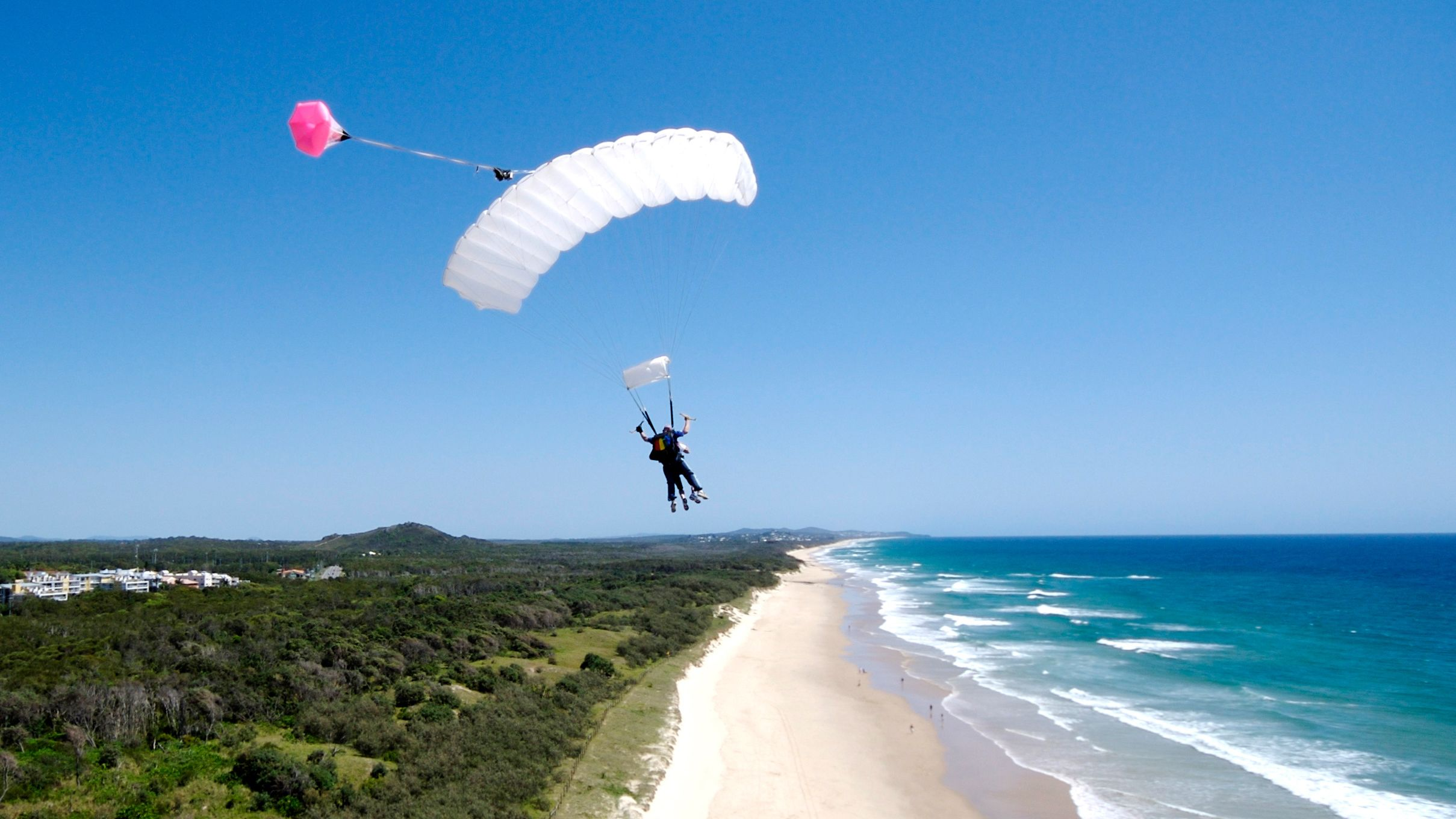 Skydivers with parachute open over Sunshine Coast beach, Australia.