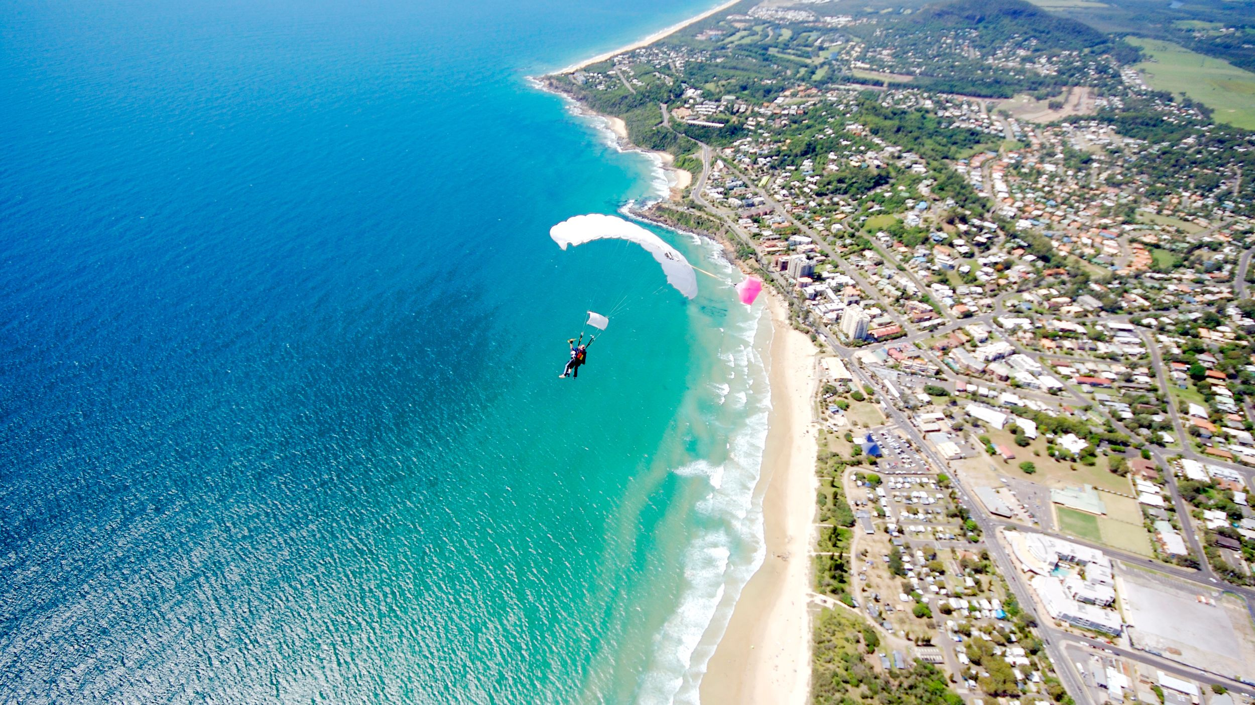 Aerial of two fastened skydivers landing over Sunshine Coast.
