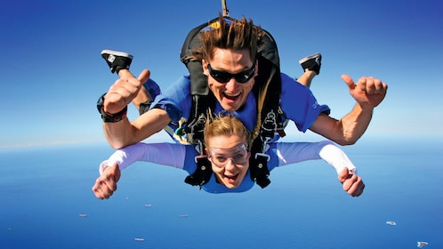 man and woman giving thumbs up while sky diving in Wollongong