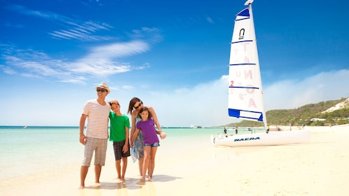 Family standing near sailboat on beach in Tangalooma