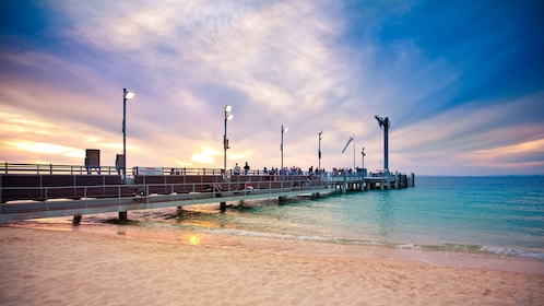 Pier on beach during sunset in Tangalooma