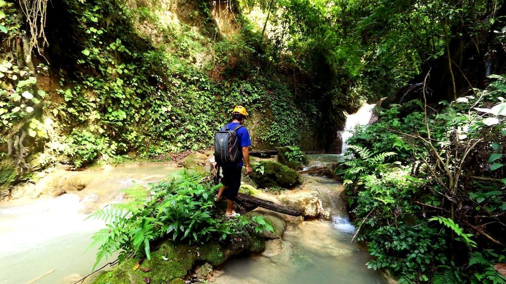 Foto 1 von 10 laden Hiker trekking through river in Laos