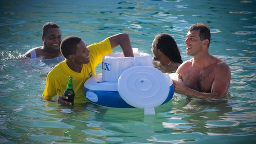 Swimming group grabbing drinks from a floating cooler in Punta Cana