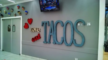 Show item 4 of 4. Large tacos sign in restaurant in Dallas