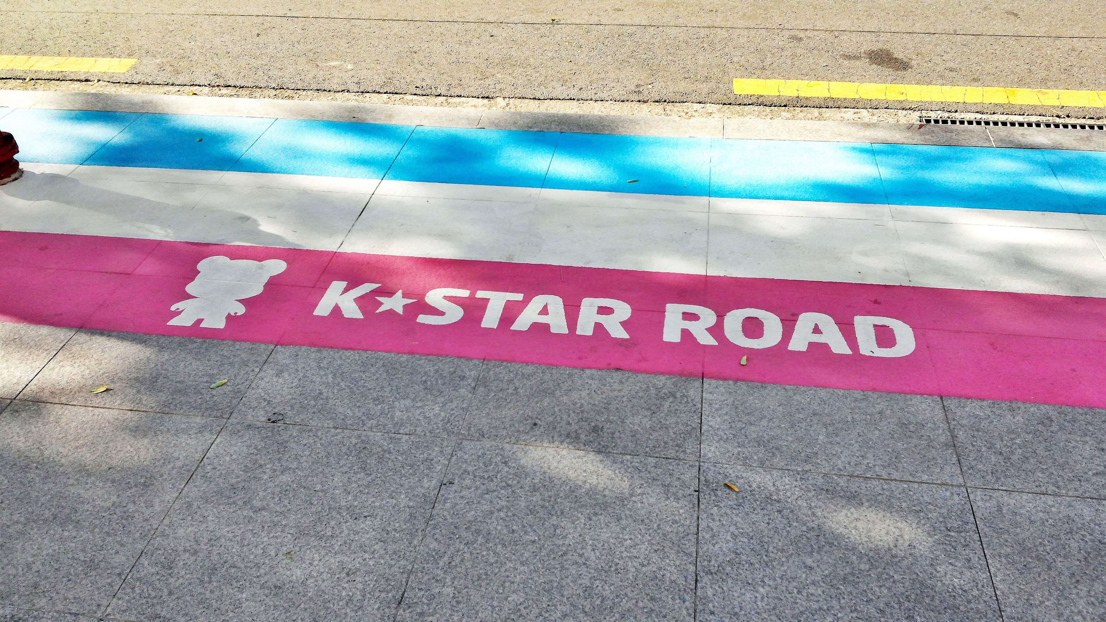 Stripes painted on the sidewalk label K Star Road in Seoul