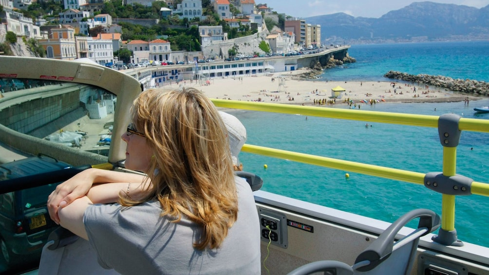 Show item 4 of 5. Woman rides a Hop On Hop Off Bus in Marseille, France, next to the coast