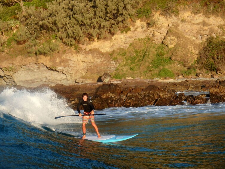 Show item 2 of 10. Paddleboarder riding a wave on Double Island