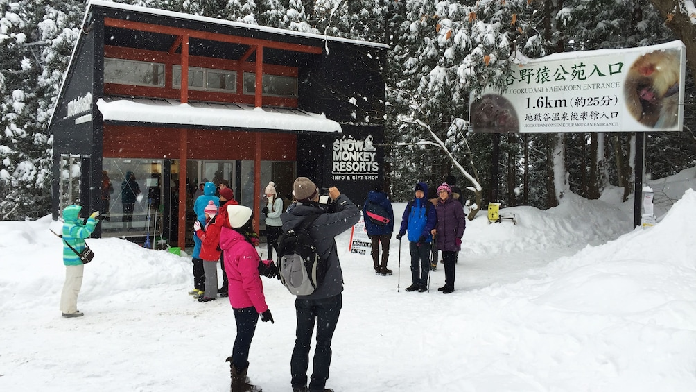 Show item 5 of 5. People taking pictures outside of Snow Monkey Resorts in Koshinetsu