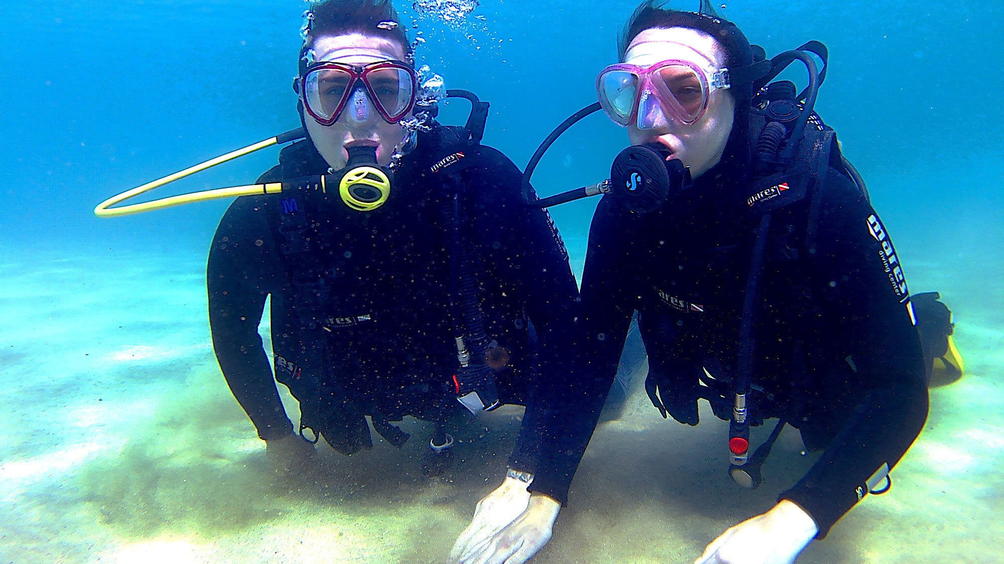 Two divers kneeling on ocean bottom in Lanzarote