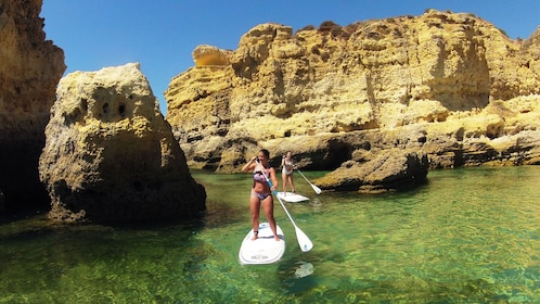 Pair of women on stand-up paddles in Algarve