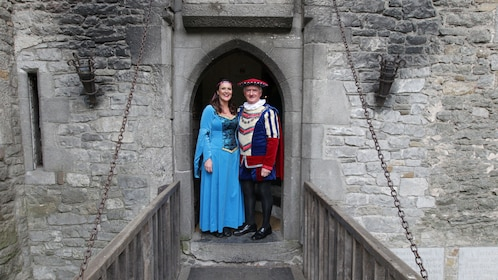 Couple in medieval costumes under an arch at Bunratty Castle in Dublin