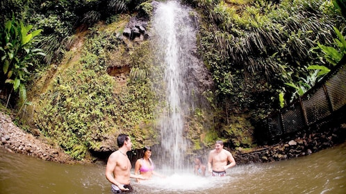 Tourists swimming at a waterfall in St. Lucia
