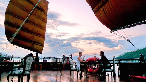 Couple eating at a table on the deck of a sailboat in Vietnam
