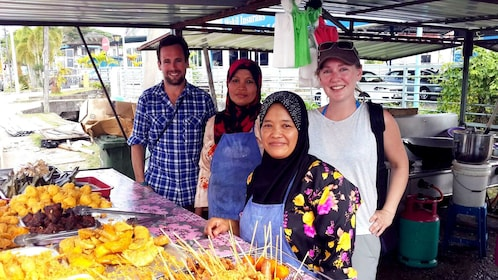 Tourist pose for photo with vendors in Borneo