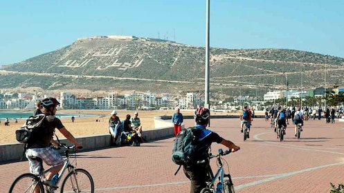People bicycling down pathway alone beach in Agadir