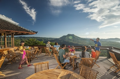 People eating on a deck overlooking the countryside of Bali