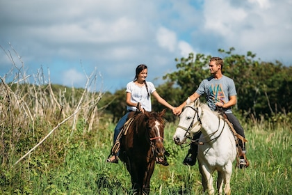 Couple holds hands while riding horses at Gunstock Ranch