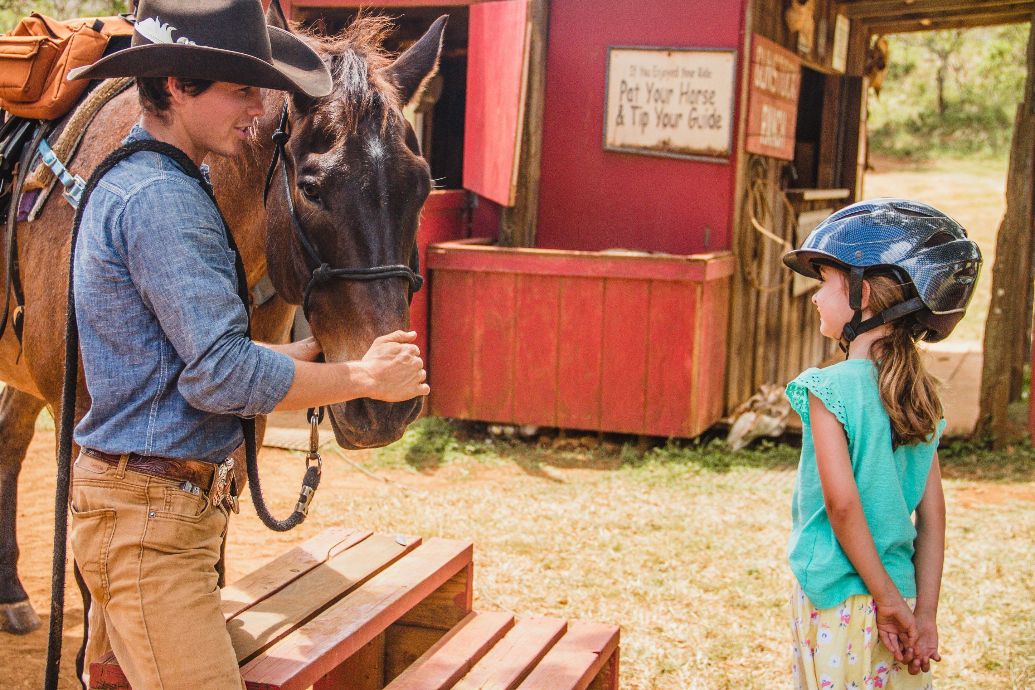 Young girl stands next to horse at Gunstock Ranch