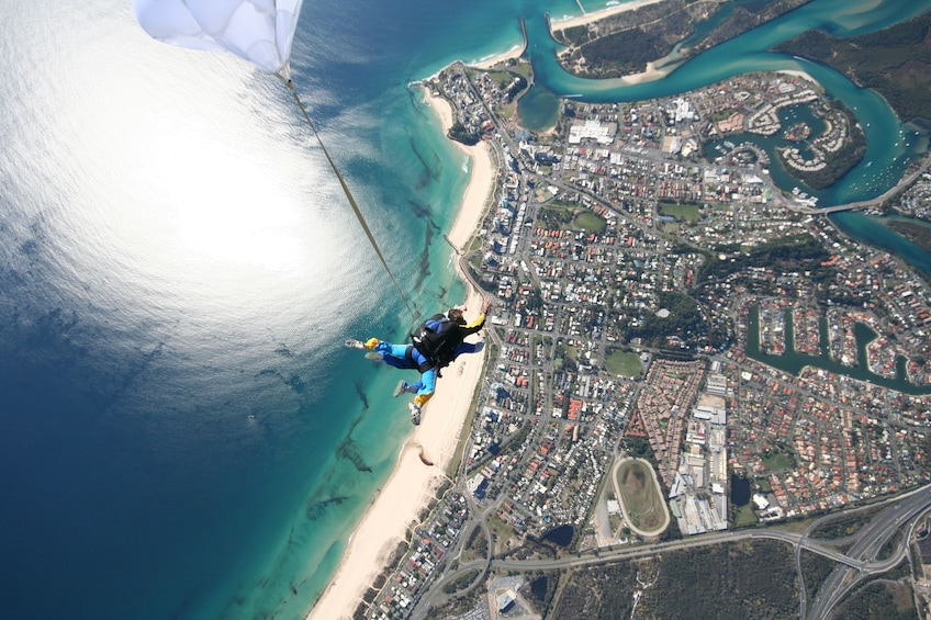 Show item 2 of 7. Skydivers deploying parachute over Gold Coast