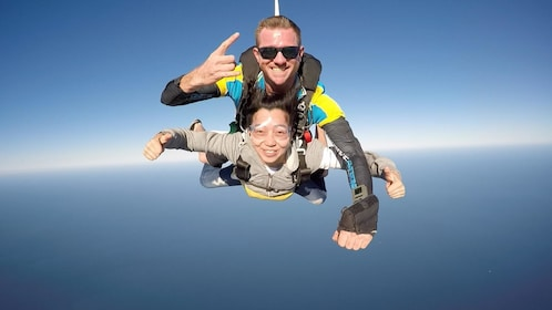Woman tandem skydiving with instructor over Gold Coast