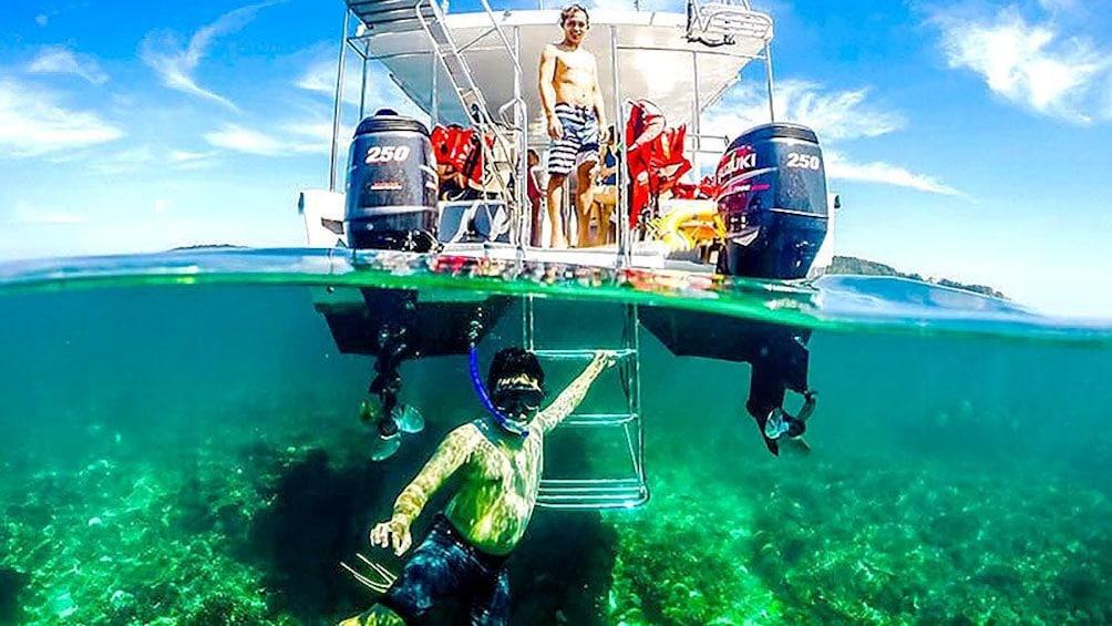 Show item 1 of 10. Snorkeler underwater near boat in Kota Kinabalu
