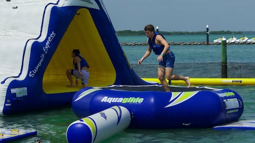Men playing on floating platforms at Hydrobounce Aquapark in Cancun