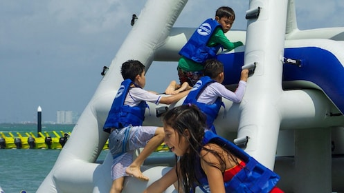 Young people climbing a floating platform at Hydrobounce Aquapark in Cancun