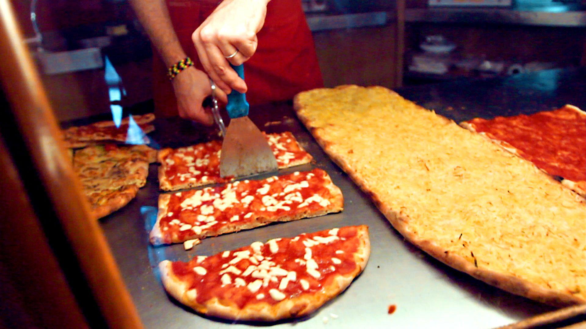 Chef cuts Pizza in a Roman Pizzeria