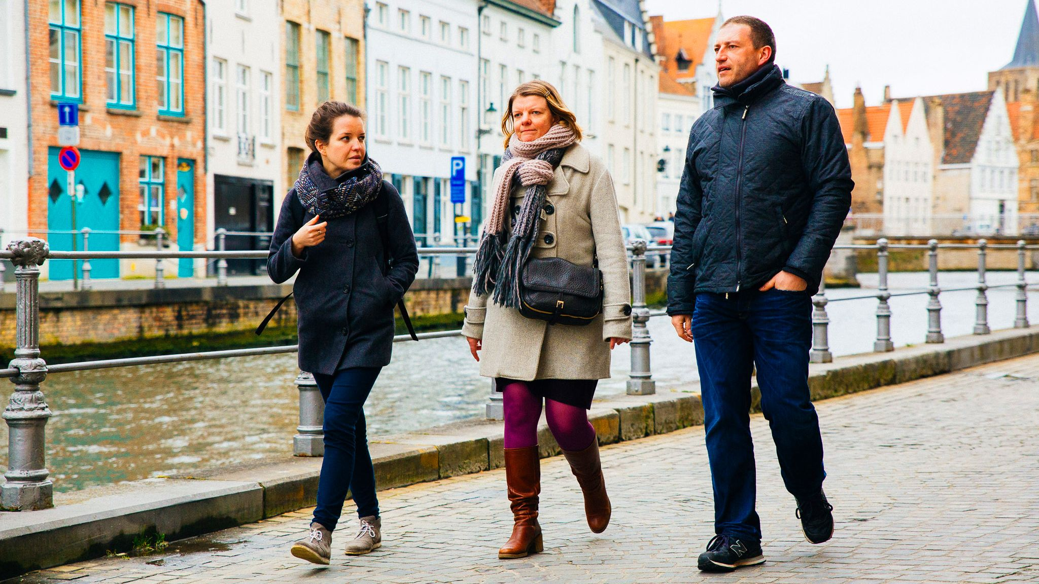 Three people tour the canals of Bruges