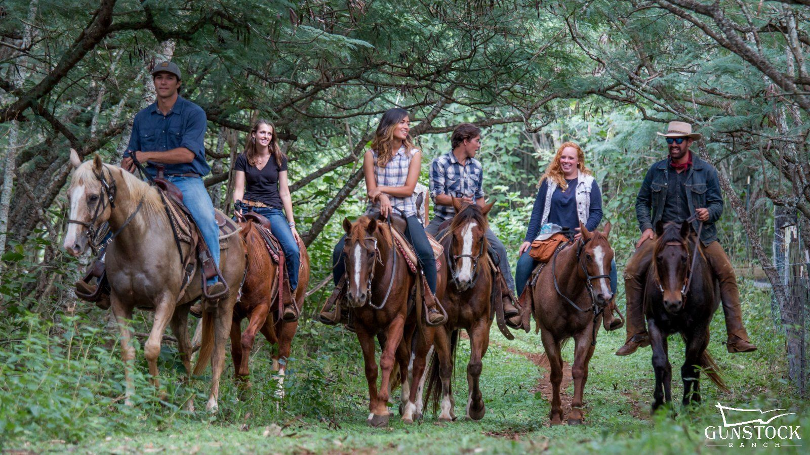 Group of people ride horses on a trail