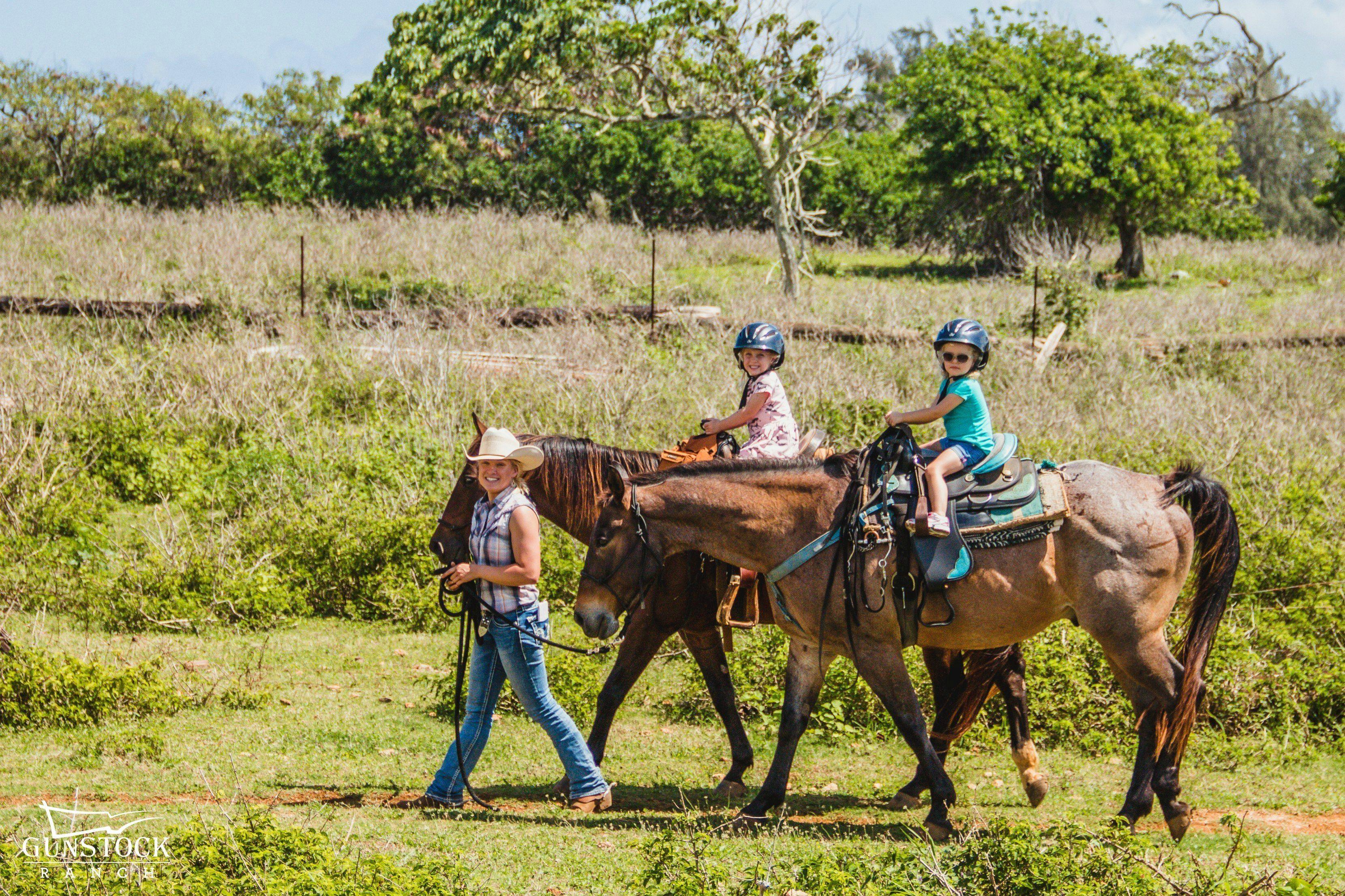 Woman leads two children on horseback