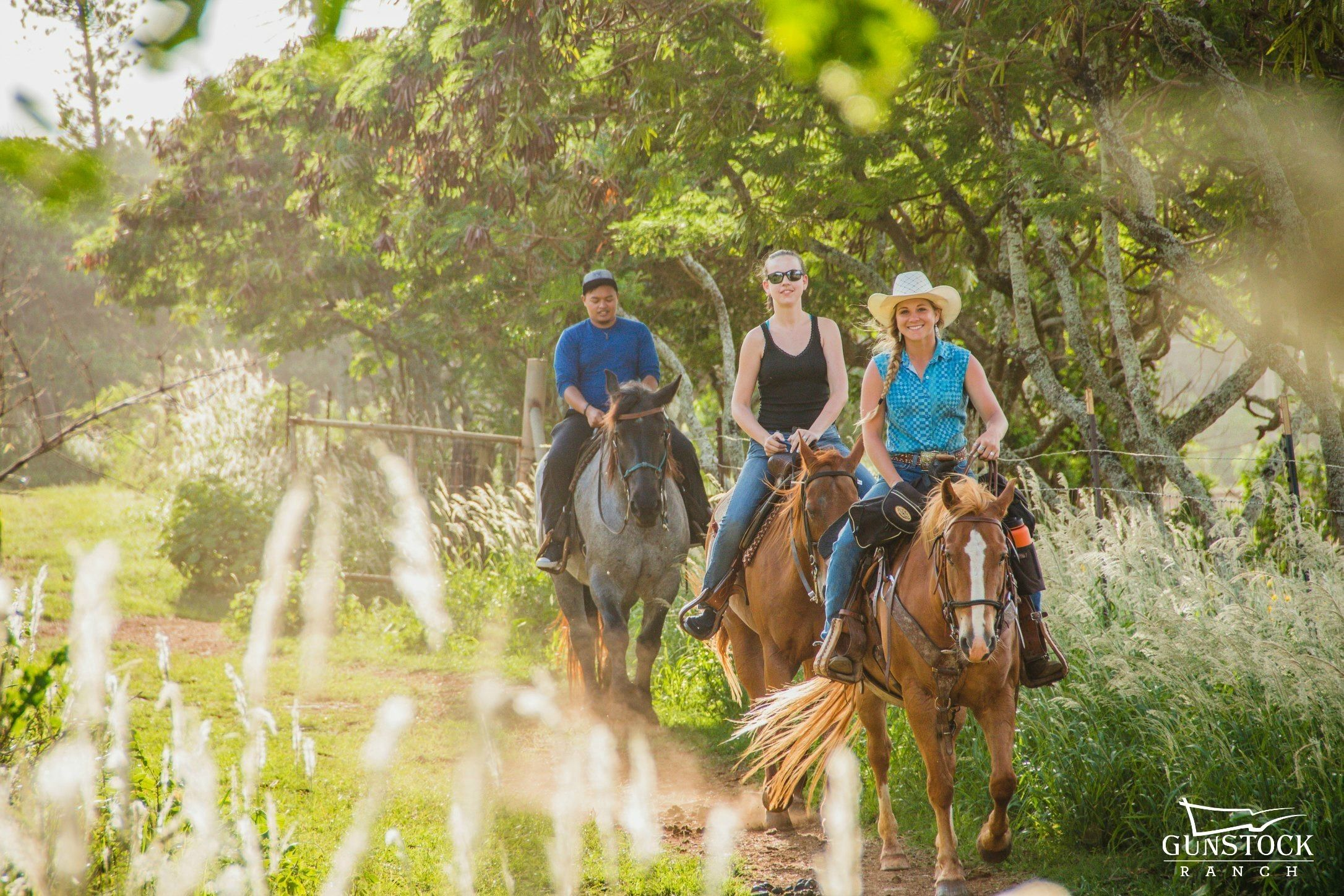 Three people on horseback on a trail at Gunstock Ranch