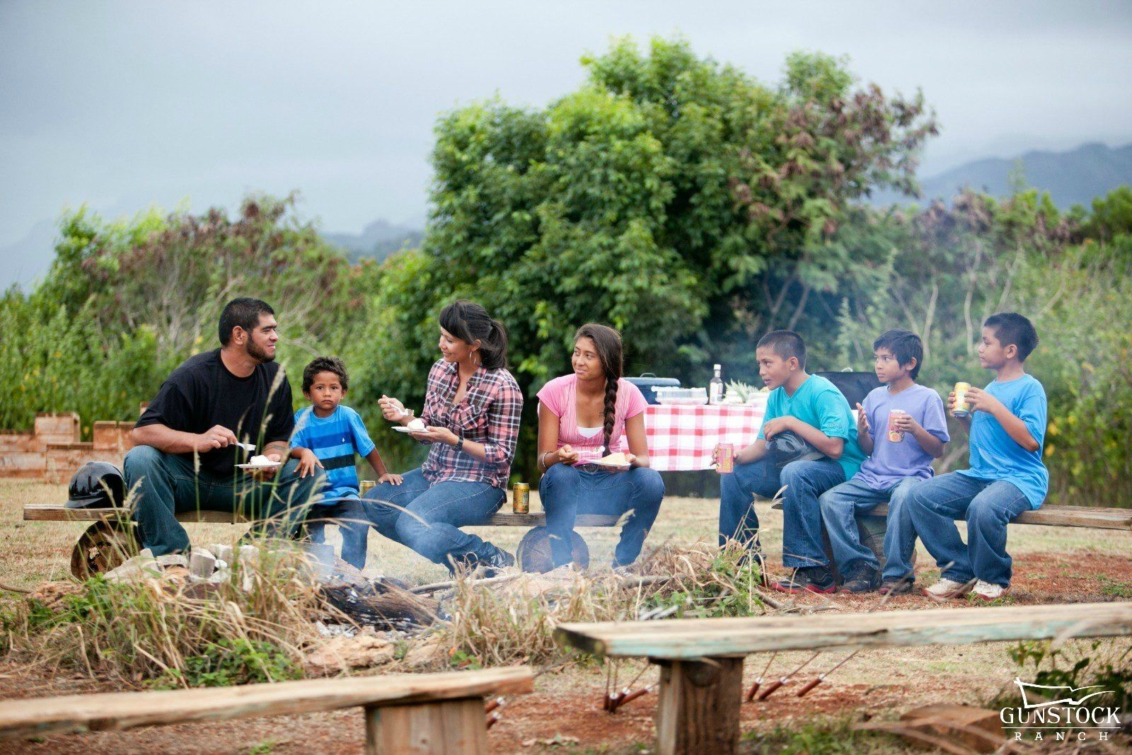 Family sits around a campfire during the day