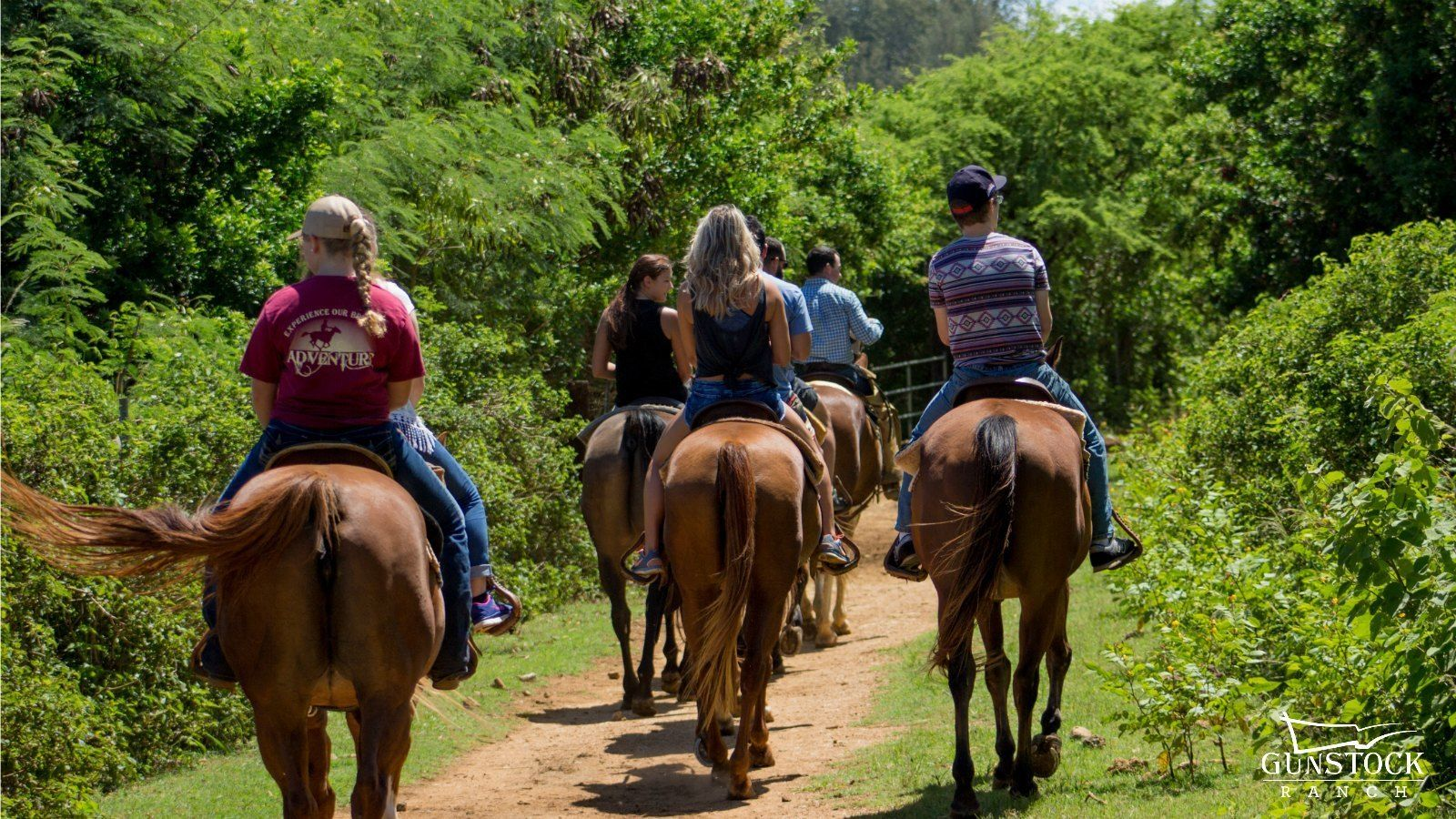 Group of people on horseback on a trail at Gunstock Ranch