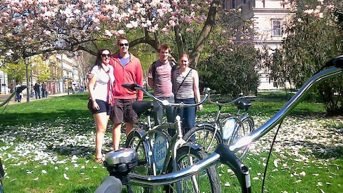 Two couples pose under flowering tree on bicycle tour in Zagreb