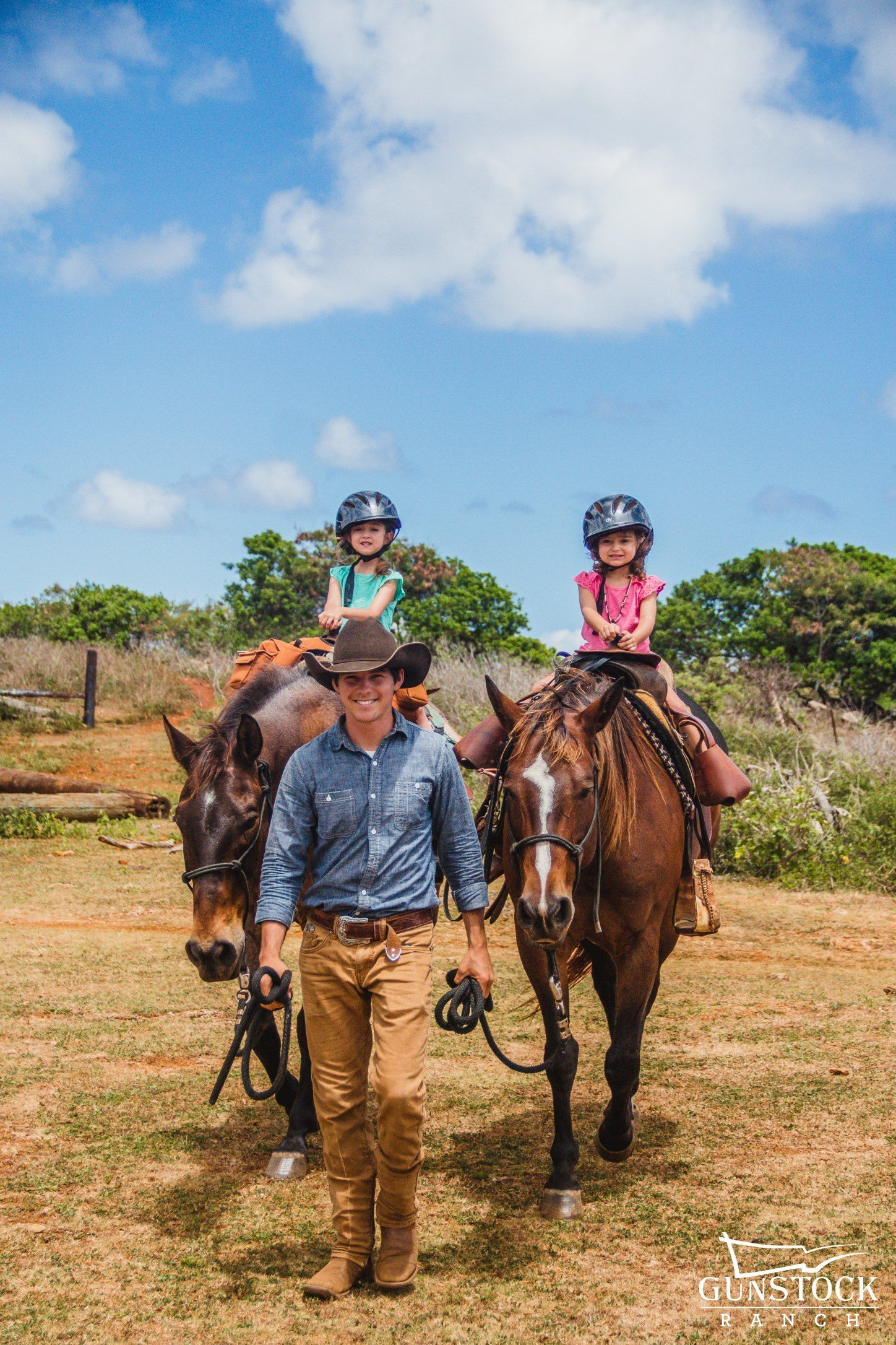 Two girls and a trainer on the Pony Ride for Kids activity in Kahuku