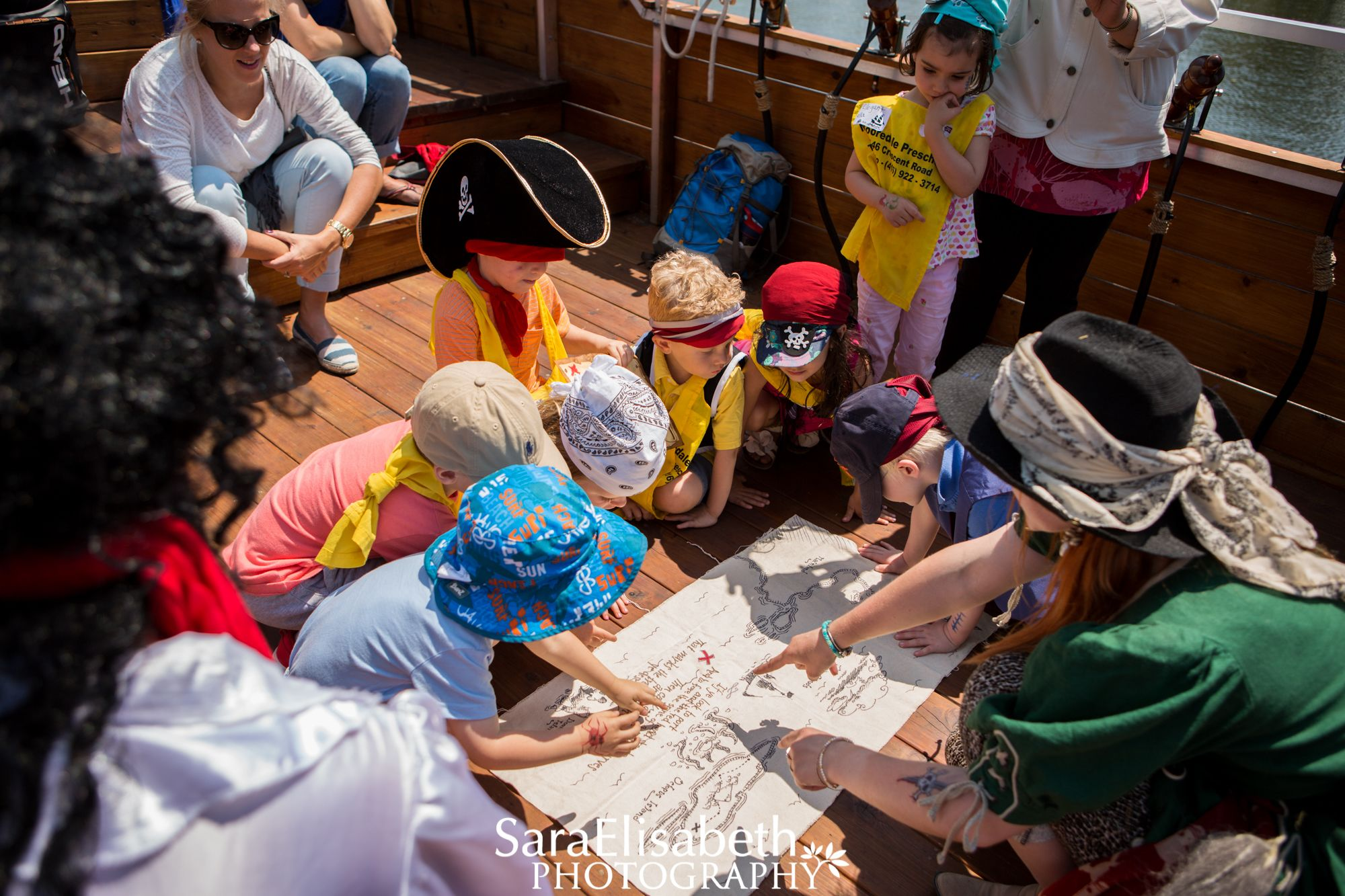 Kids looking at a map together at the Pirate Life Adventure Theatre in Toronto, Canada